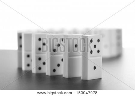 Line of dominoes standing on gray background