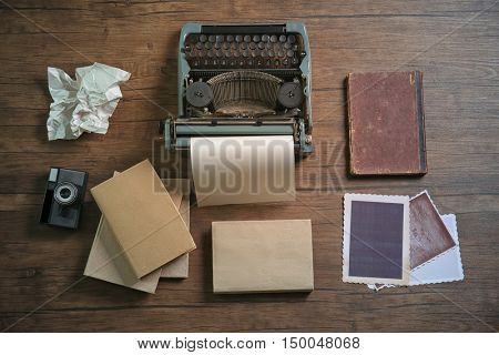 Retro typewriter with camera and photos on wooden background