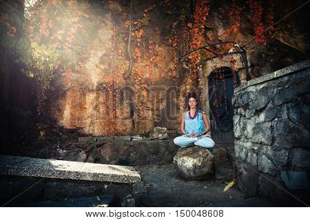 young woman meditate on the rock outdoor in front old wall and cliff autumn  day