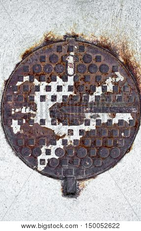 Old rusty corroded manhole cover on a white road concrete