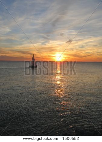 Sunset Over The Sea With A Sailing Boat Cruising, France