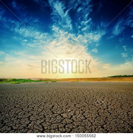 sunset in deep blue sky over drought earth