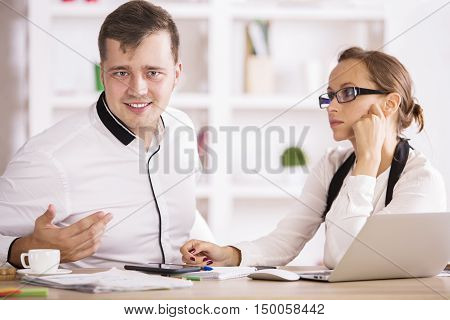 Handsome young man and woman in formal shirts sitting at office desk with laptop computer coffee cup paperwork and other items