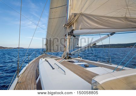 New clear sailing boat teak deck and hoisted sails, view from the cockpit to the bow. Sardinia, Italy.