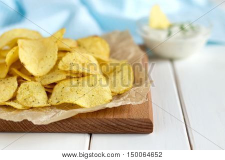Potato Chips With A Dipping Sauce On A White Wooden Table.