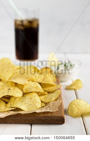 Potato Chips On A Cutting Board With Dipping Sauce And Drink.