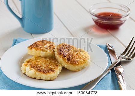 Pancakes Of Cottage Cheese With A Sweet Sauce On A White Table.