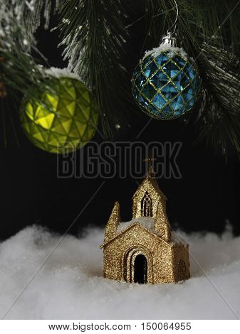 A night scene of a little church ornament under the branches of a Christmas tree.  On a black background.
