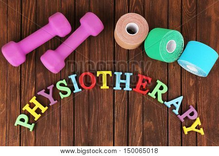 Medical bandage rolls, dumb bells and word physiotherapy made with plastic letters on wooden background