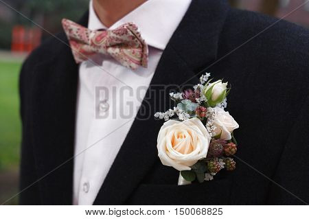 Ivory roses and blackberries boutonniere on black suit of the groom