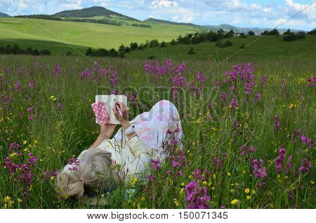 Blonde woman lying on a spring field with lush wildflowers holding her cell phone and writing in her note pad