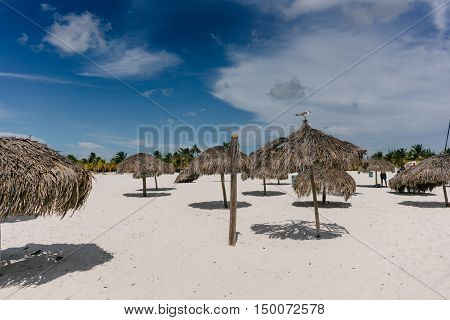 Beach umbrellas made of palm branches on the shores of the Caribbean Sea on the white sand beach of Cayo Largo, Cuba