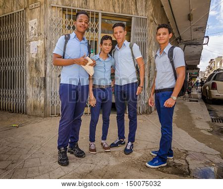 HAVANA - CUBA JUNE 10, 2016: School boys in uniform pose for a photo at the corner of San Rafael and Amistad streets in a popular shopping district for young people in La Habana Vieja.