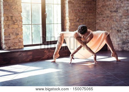 Feel the dance inside. Masterful confident beautiful dancer bending down and keeping her arms crossed while standing on tiptoes