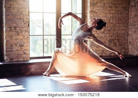 Graceful movements. Talented good looking young woman holding up her hand and bending backwards while dancing