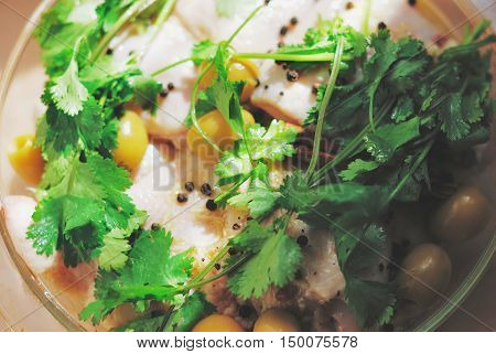Raw chicken pieces seasoned with pepper and garnished with olives and parsley before cooking on a glass dish top view closeup.