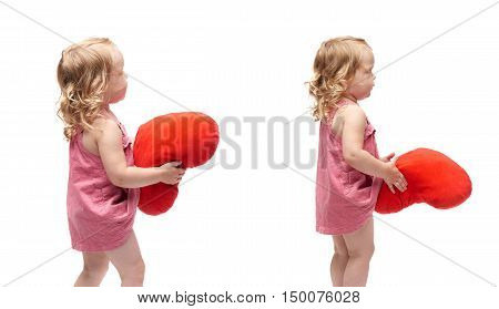 Young little girl with curly hair and red plush heart in pink dress standing over isolated white background