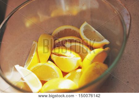 Pile of lemons cut into wedges in a glass dish on the table.