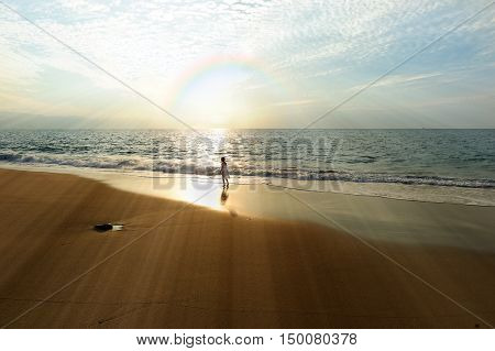 Ocean rainbow girl is a young girl on the beach looking at a rainbow burst with awe and wonder.