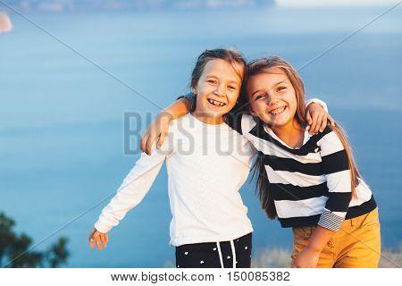 Two smiling children hugging over blue sea