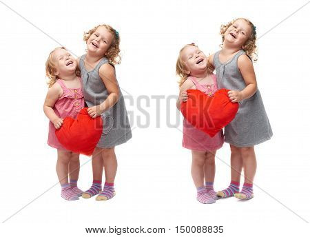 Couple of young little girls sisters with curly hair in gray and pink dress holding red plush heart and standing over isolated white background