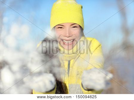 Winter fun girl playful throwing snow at camera portrait. Asian woman face closeup with yellow beanie knit hat and white gloves playing with snowflakes. Happy snowball snow fight wintertime concept.