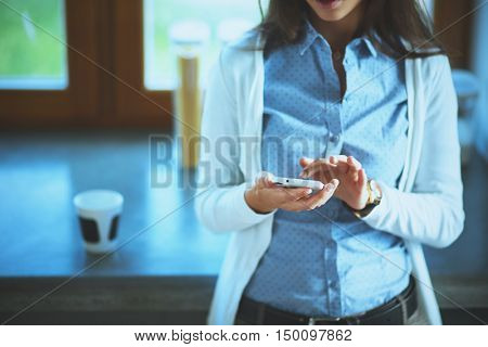 Happy woman drinking tea in the kitchen at home and talking on the phone