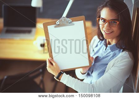 Young woman standing near desk with laptop holding folder