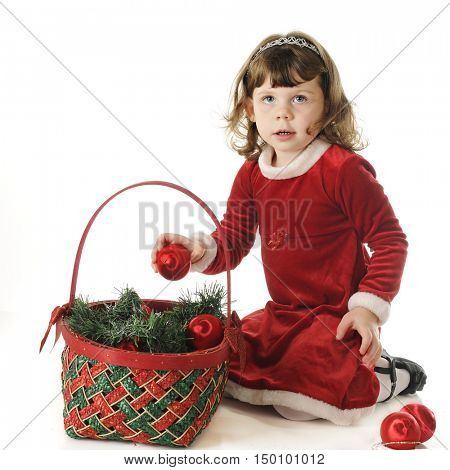 An adorable preschooler kneeling in her Christmas dress as she playing with a Christmas basket and bulbs.  On a white background.