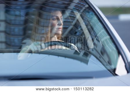 young adult blonde beautiful woman driving a car, view from behind a glass