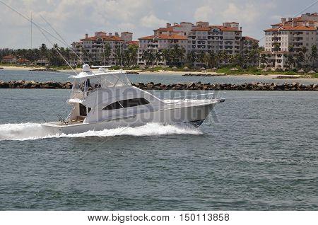 Upscale  sport fishing boat cruising past luxury condominium buildings on a private island in Mimi,Florida.