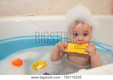 The beautiful little girl bathes in a blue bath with a toy