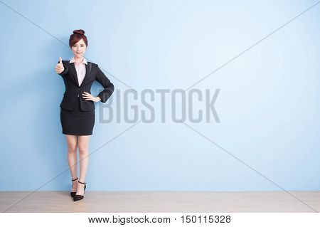 business woman is smile to you and thumbs up with blue background asian
