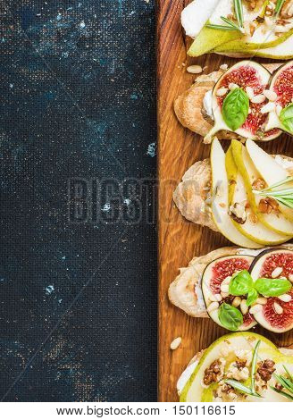 Crostini with pear, ricotta cheese, figs, nuts and fresh herbs. Breakfast toasts or snack sandwiches on rustic wooden board over dark blue grunge plywood background. Top view, copy space