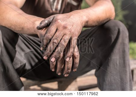 Charcoal-burners worker man with dirty hands. Worker Man with Dirty Hands.
