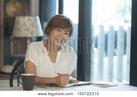 asian woman smiling face education and working at home concept relaxing on working table