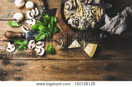 Italian style dinner. Creamy mushroom pasta spaghetti in cast iron pan with Parmesan cheese, fresh basil and pepper over old rustic wooden background. Top view, copy space, horizontal composition