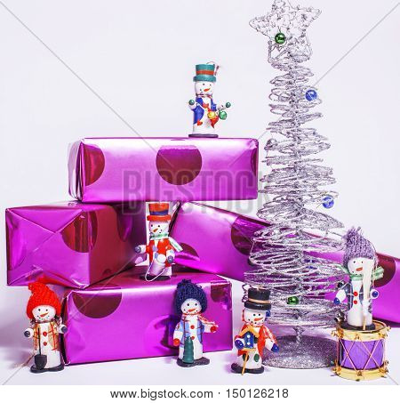 little sweet stylish snowmen toys with purple gifts and silver tree, isolated on white close up, sants claus red hat, postcard
