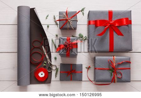 Gift wrapping. Packaging modern christmas present. Lots of gift boxes in stylish modern gray paper, decorated with red satin ribbon bows. Christmas and winter holidays concept, top view, flat lay