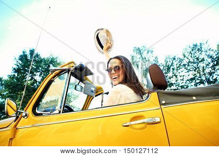 Portrait of Young girl driving cabriolet at sunset.