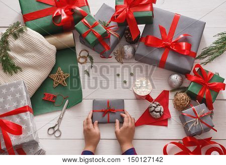 Winter holidays celebrating. Gift wrapping. Packaging modern christmas present boxes in paper with satin red ribbon. Top view of hands on white wood table with fir tree branches, decoration of gift.