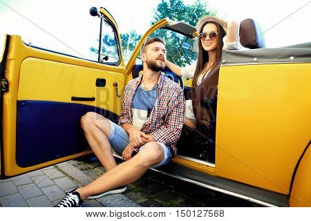 Spending great time together. Beautiful young couple talking and smiling while standing near their new convertible