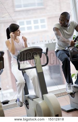 Two People Doing Biking Exercises At Gym