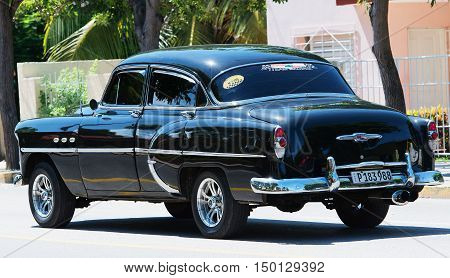 Varadero, Cuba - September 11, 2016:  black American Classic Car Dirves in Varadero City, Cuba