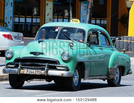 Varadero, Cuba - September 11, 2016:  green American Classic Car Dirves in Varadero City, Cuba