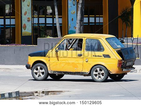 Varadero, Cuba - September 11, 2016:  Yellow Classic Car Dirves in Varadero City, Cuba