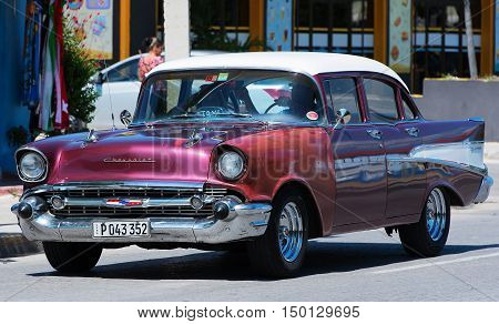 Varadero, Cuba - September 11, 2016:  Red American Classic Car Dirves in Varadero City, Cuba