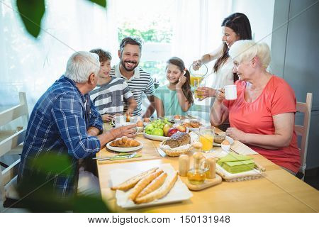 Happy multi-generation family sitting at breakfast table