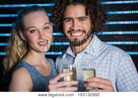 Portrait of smiling couple holding a glass of champagne in bar
