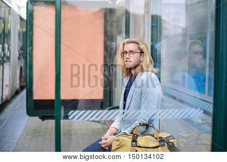 Handsome man waiting at the bus stop
